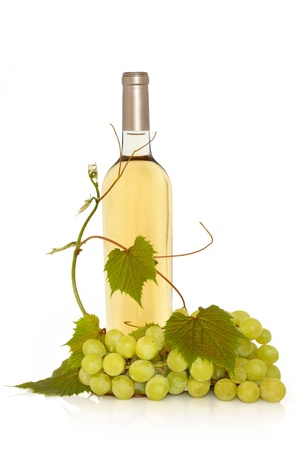 white wine:  White wine in a bottle with fresh grapes on the vine with leaf sprigs isolated over white background.