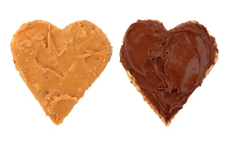 Peanut butter and chocolate spread on heart shaped bread isolated over white background.