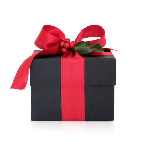 Christmas gift box  decorated with red satin ribbon and bow with holly leaf and berry sprig isolated over white background. Stock Photo - 10679070