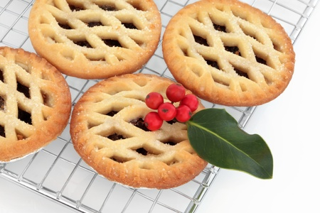 Mince pie cakes with holly berry leaf sprig on a stainless steel baking rack,  over white background. photo