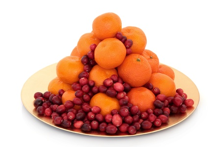 cranberry fruit: Cranberry and mandarin christmas fruit arrangement on a gold plate isolated over white background.