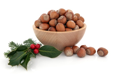 cobnut: Hazelnuts in a wooden bowl with winter holly berry and pine fir leaf sprig isolated over white background.