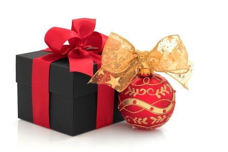 Christmas gift box with red satin ribbon and sparkling bauble with gold bow, isolated over white background. photo