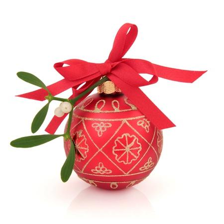 muerdago: Navidad con muérdago chuchería brillo rojo y oro con la cinta y un arco aislado sobre fondo blanco. Foto de archivo