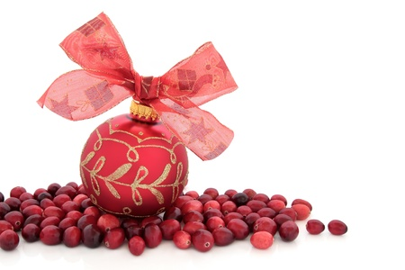cranberry fruit: Christmas red bauble with bow and cranberry fruit isolated over white background.