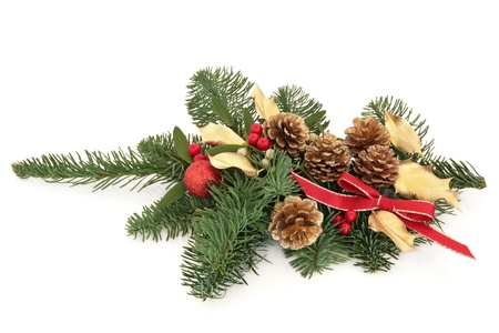 Christmas decoration of mistletoe, gold holly and pine cones with blue spruce fir leaf sprig, bauble,and red bow isolated over white background. photo