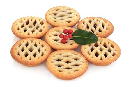 carne picada: Navidad pelos pasteles pastel con una ramita de acebo de hoja baya dispuestas en un círculo aislado sobre fondo blanco. Enfoque selectivo. Foto de archivo