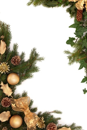 Christmas border of gold bauble, bow, holly and oak leaf decorations, pine cones and spruce fir with ivy leaves, isolated over white background. photo