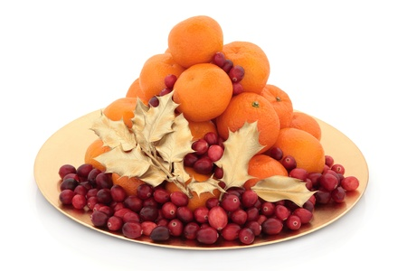 cranberry fruit: Christmas orange and cranberry fruit arrangement, with gold holly leaf sprigs on a gold plate isolated over white background. Stock Photo