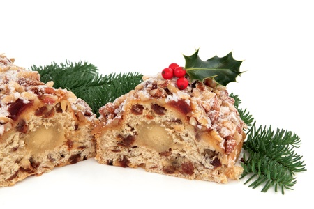 fruitcake: Stollen christmas cake with holly berry and blue pine fir leaf sprigs isolated over white background. Stock Photo