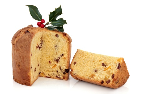 Panettone christmas cake with slice decorated with holly berry leaf sprig  isolated over white background.