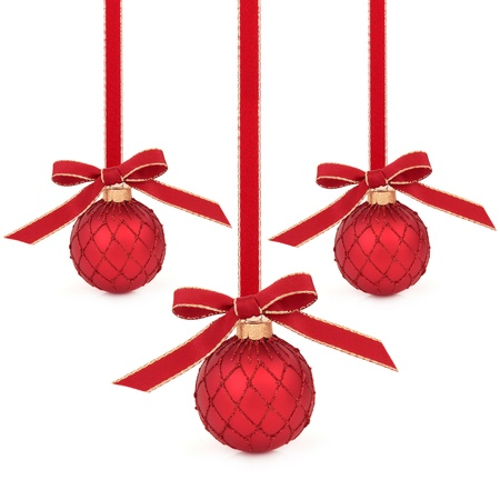 dangling: Christmas bauble decorations dangling with red and gold ribbon and bow isolated over white background.