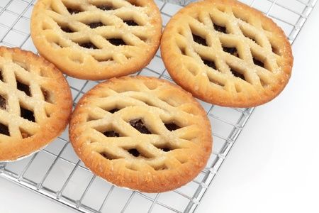 minced pie: Christmas latticed mince pie group on a baking metal cooling rack over white background. Selective focus