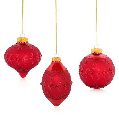 Christmas red bauble trio with glitter designs dangling from gold twine isolated over white background. photo