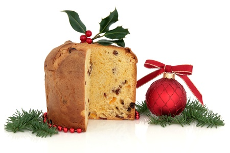 Panettone christmas cake, holly and red bauble decoration with spruce pine fir leaf sprig  isolated over white background. photo