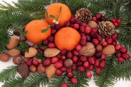 mandarin: Christmas mandarin orange aChristmas mandarin orange and cranberry fruit, nuts, holly leaf sprigs, mistletoe, pine cones and blue spruce fir forming an arrangement over white background. Stock Photo