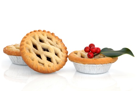 mincing: Christmas mince pie group with holly berry leaf sprig isolated over white background.