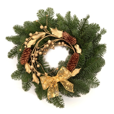 Christmas wreath of blue spruce fir with pine cones, golden holly, ribbon and balls isolated over white background. photo