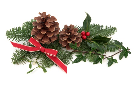 Christmas decoration of holly, ivy, mistletoe, pine cones and spruce fir leaf sprig with red ribbon isolated over white background.