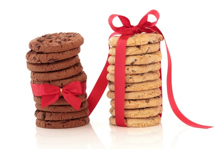 Chocolate chip cookie stacks tied with red satin ribbon and bows, isolated over white background. photo