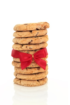 Chocolate chip cookie stack tied with a red satin ribbon and bow, isolated over white background. photo