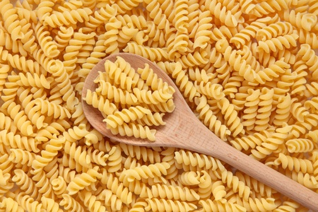 Fusilli pasta with a wooden spoon forming a textured background. Stock Photo - 11378078