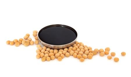Les fèves de soja, sauce de soja foncée dans un bol en acier inoxydable isolé sur fond blanc.