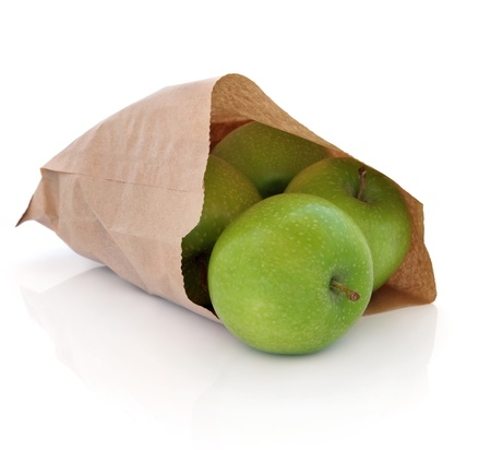 Green apples in a brown paper bag isolated over white background. Granny Smith variety. photo