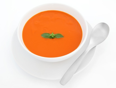 Tomato soup with basil herb leaf in a porcelain bowl with plate and stainless steel spoon isolated over white background. Stock Photo - 11492036
