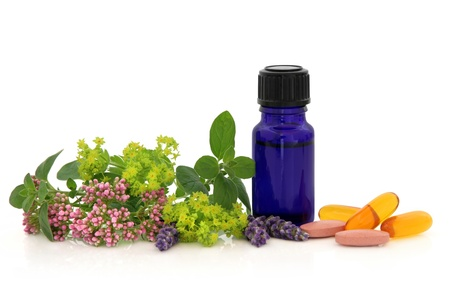 Lavender, valerian and ladies mantle herb flower heads with marjoram leaf sprigs, aromatherapy bottle and vitamin pills isolated over white background. Stock Photo - 11492027