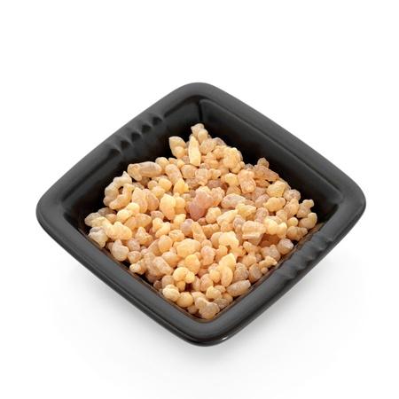 incienso: Mirra resina en un plato cuadrado negro aisladas sobre fondo blanco.