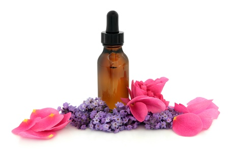 Rose flower petals and lavender herb flowers with aromatherapy brown glass dropper bottle isolated over white background. Lavandula and rosa rugosa. Banco de Imagens