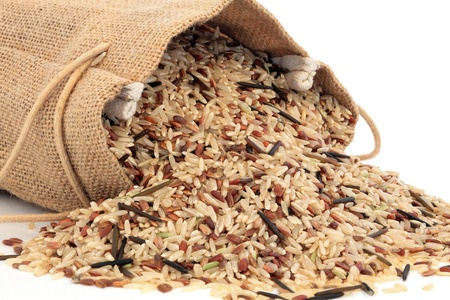 Wild rice in a hessian sack and loose over white background. photo