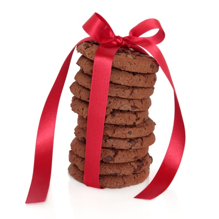 Chocolate chip cookie stack tied with a red satin ribbon isolated over white background. photo