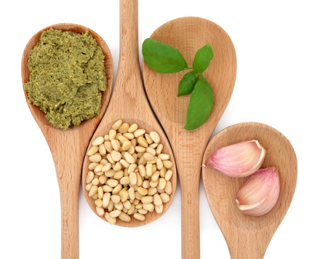 cloves: Pesto sauce and ingredients of pine nuts, basil herb leaf and garlic cloves in wooden spoons isolated over white background. Stock Photo