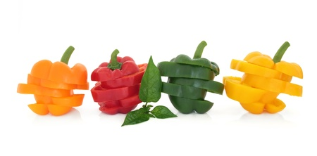 red chilli: Orange, red, green and yellow sliced bell pepper vegetables in layered stacks with leaf sprig isolated over white background.