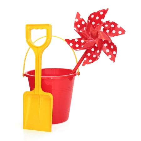 spades: Toy windmill with beach bucket and spade in red and yellow colours isolated over white background. Stock Photo