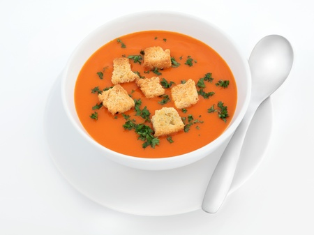 Tomato soup with toasted croutons and parsley herb in a porcelain bowl with plate with spoon over white background. Stock Photo - 12420284