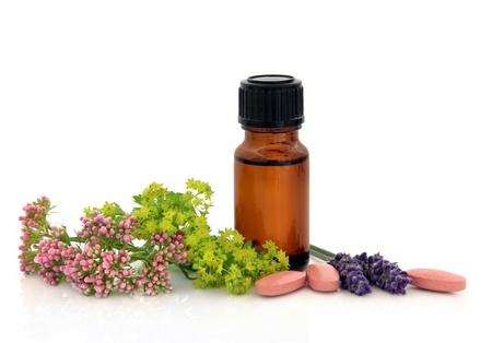 valerian: Erbe lavanda, valeriana, signore capolini mantello e bottiglia aromaterapia con le pillole di medicina alternativa su sfondo bianco.