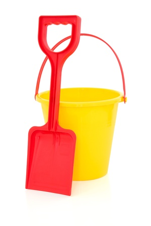 Beach bucket and spade toys in red and yellow isolated over white background. photo