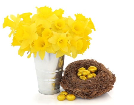 Easter egg group wrapped in gold foil in a natural bird  nest with daffodil flowers in an aluminum vase over white background. photo