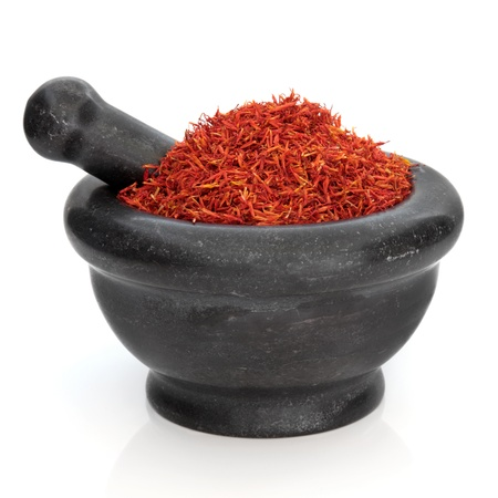 saffron: Saffron used in traditional chinese herbal medicine in a black granite mortar with pestle isolated over white background. Hong Hua.  Flos carthami tinctori.