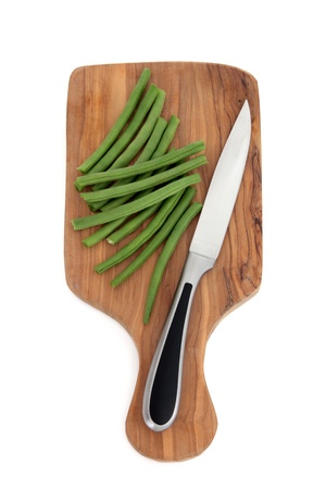 Green bean vegetables  on an olive wood chopping board with stainless steel carving knife over white background. photo