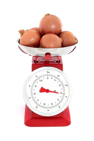 kitchen scale: Onion vegetables weighing three kilos on a red metal set of retro scales against white background  Stock Photo