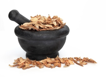 licorice: Licorice root used in traditional chinese herbal medicine in a black granite mortar with pestle isolated over white background  Gan cao  Stock Photo