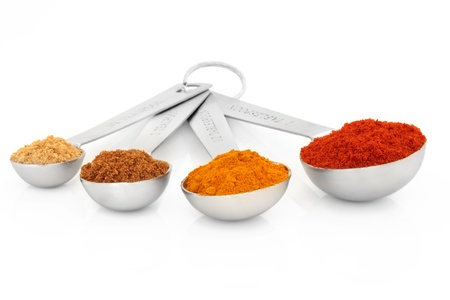 measuring spoons: Spice selection of ground ginger, mace, turmeric and cayenne pepper in measuring spoons  over white background