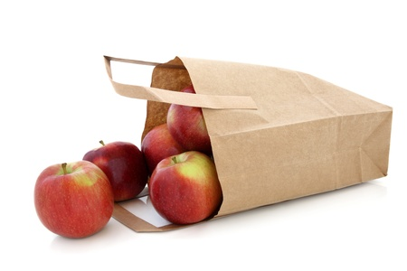 Apple fruit in a brown paper recycled carrier bag isolated over white background  Red Dessert variety  photo