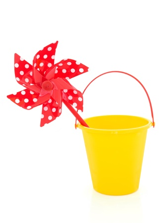 Toy windmill in red with polka dots and yellow plastic bucket isolated over white background  photo