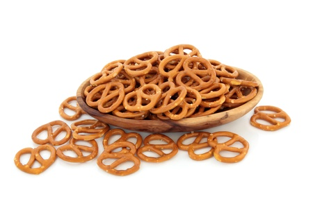 pretzels: Pretzel cracker biscuits in an olive wood bowl and scattered isolated over white background