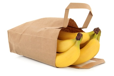 brown banana: Banana fruit in a brown paper recycled grocery bag isolated over white background  Stock Photo